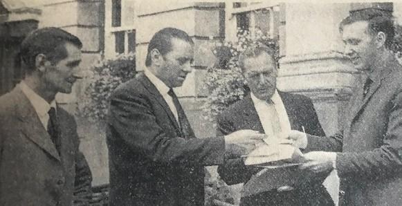 Roy Cotter presents the petition to Coun John Cotter (right). Pictured with fellow organisers, Frank Lester (left) and Roy Walker (third left)