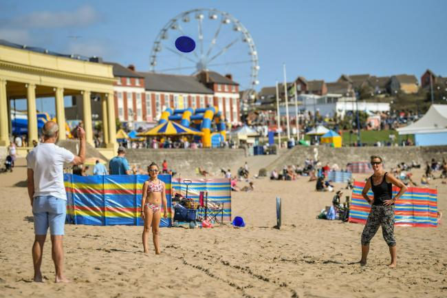 People play frisbee on the beach at Barry Island, Wales, enjoying the Autumn sunshine.  PA Photo. Picture date: Sunday September 13, 2020. Photo credit should read: Ben Birchall/PA Wire.