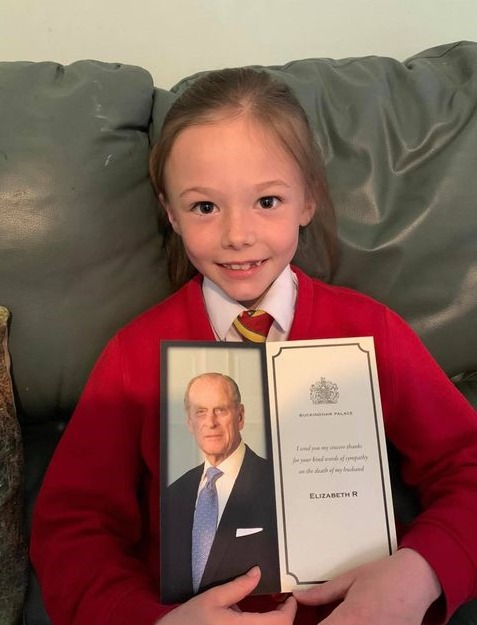 A smiling Ellie with her reply from Queen Elizabeth II