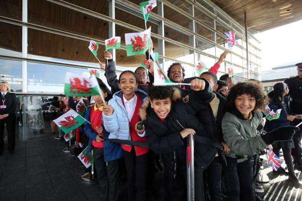 Barry And District News: Children from Mount Stuart Primary School wave flags outside the Senedd. Picture: Huw Evans Picture Agency