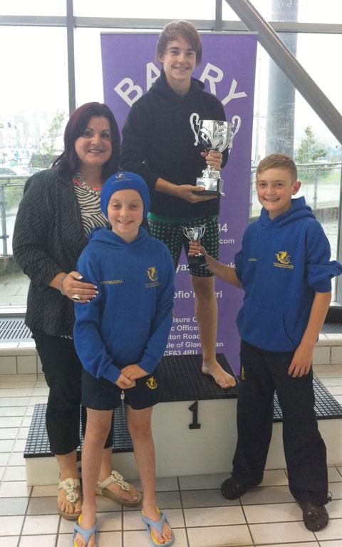 Ryan Connor being presented with the Brian Hardwick cup for the best 12-year-old boy in the competition by Brian's daughter Rhian and her two sons.