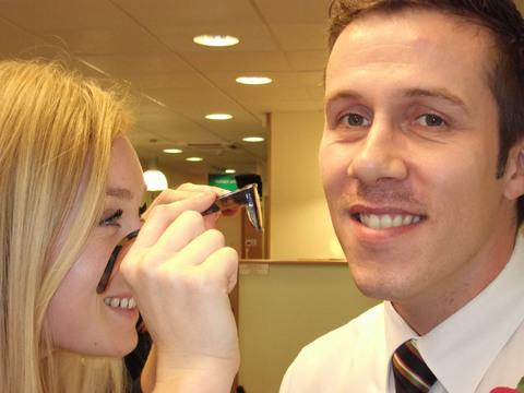 EYE CAN HARDLY SEE IT: Dispensing optician Lauren Richards inspects Specsavers Barry director Jamie Pullen's early Movember effort