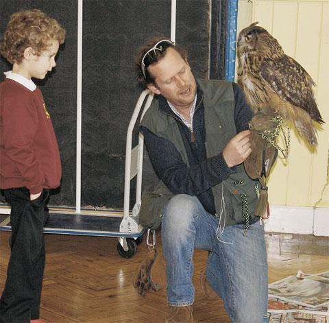 BIRD IN THE HAND: Buzz takes centre perch alongside handler Jamie and pupil Curtis.