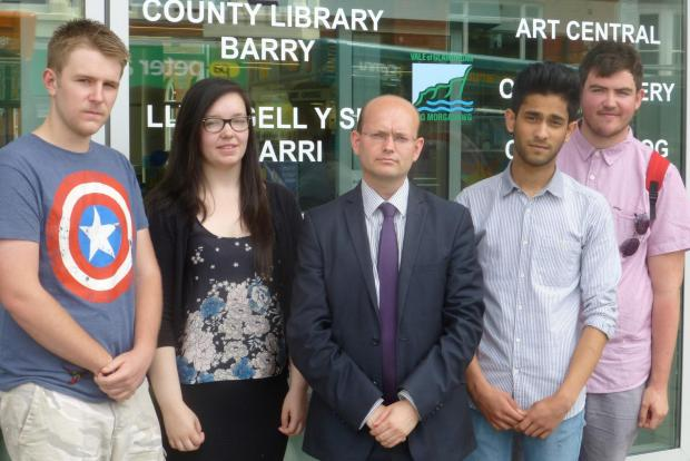 Barry And District News: STUDENTS' VIEWS: Fighting opening hours cuts .  . . Plaid Cymru councillor Ian Johnson (centre), with St David's College Sixth Form students, from left: George Moyle, Adele Saif, Akshay Petta and Jake Harvey.