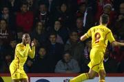 Liverpool's Raheem Sterling, left, celebrates opening the scoring