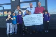 John Little of Dow Corning and his wife Tess presenting a cheque for £2,350 to Chris Britton headmaster of Ysgol Y Deri with some of the children