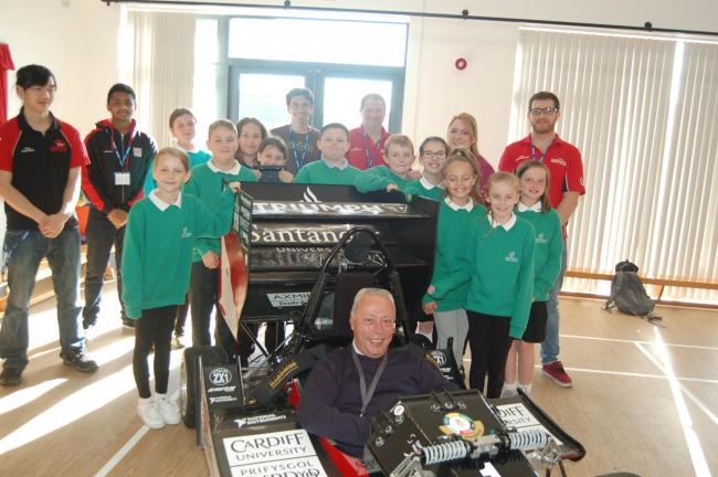 Head teacher Ian Williams, seated in car, with Year 6 pupils, Year 6 class teacher Mrs Barnfield, and  Cardiff University students