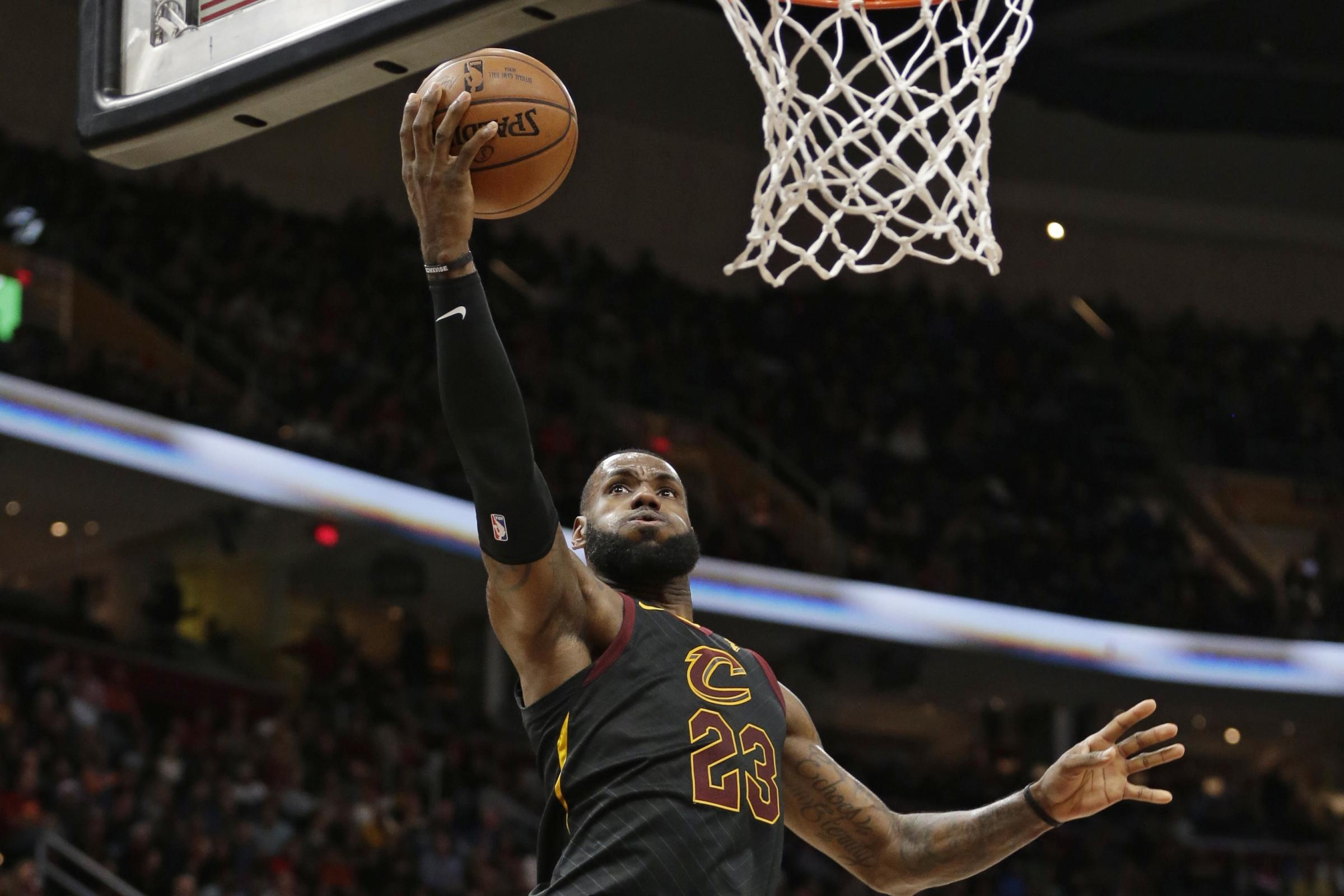 LeBron James, left, drives to the basket (Tony Dejak/AP)