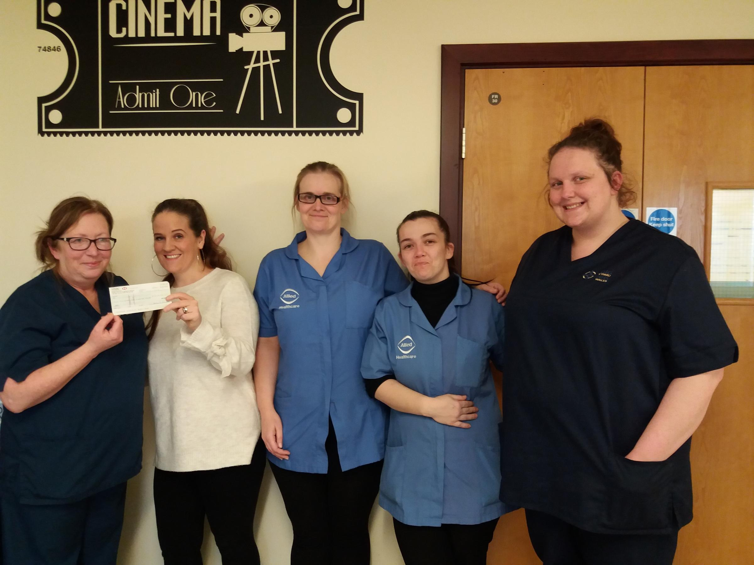Members of Allied Healthcare present Barry Hospital's Baruc Ward with the cheque