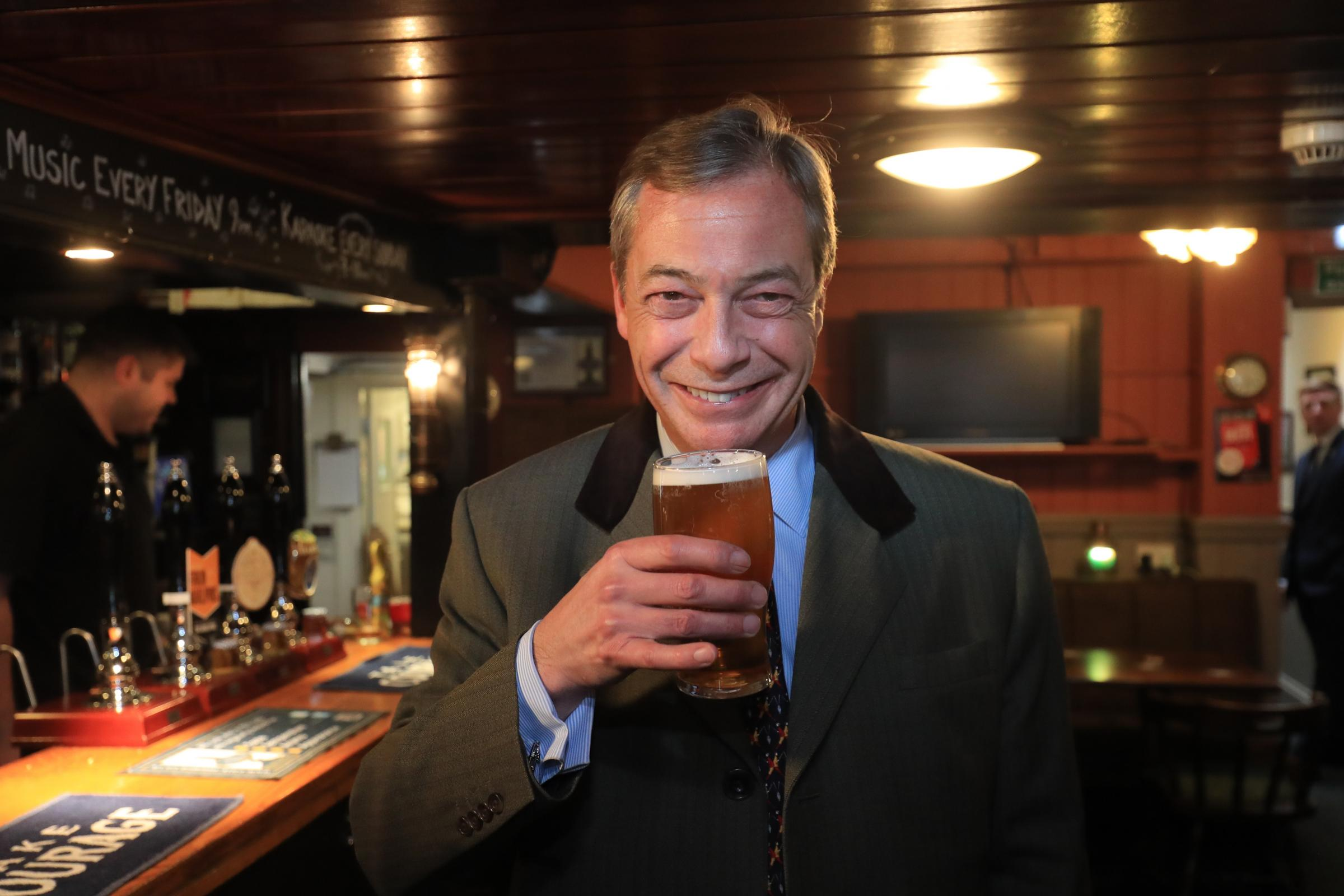 Nigel Farage enjoys a pint in Shoreham, West Sussex, during a walkabout ahead of a Brexit Party rally